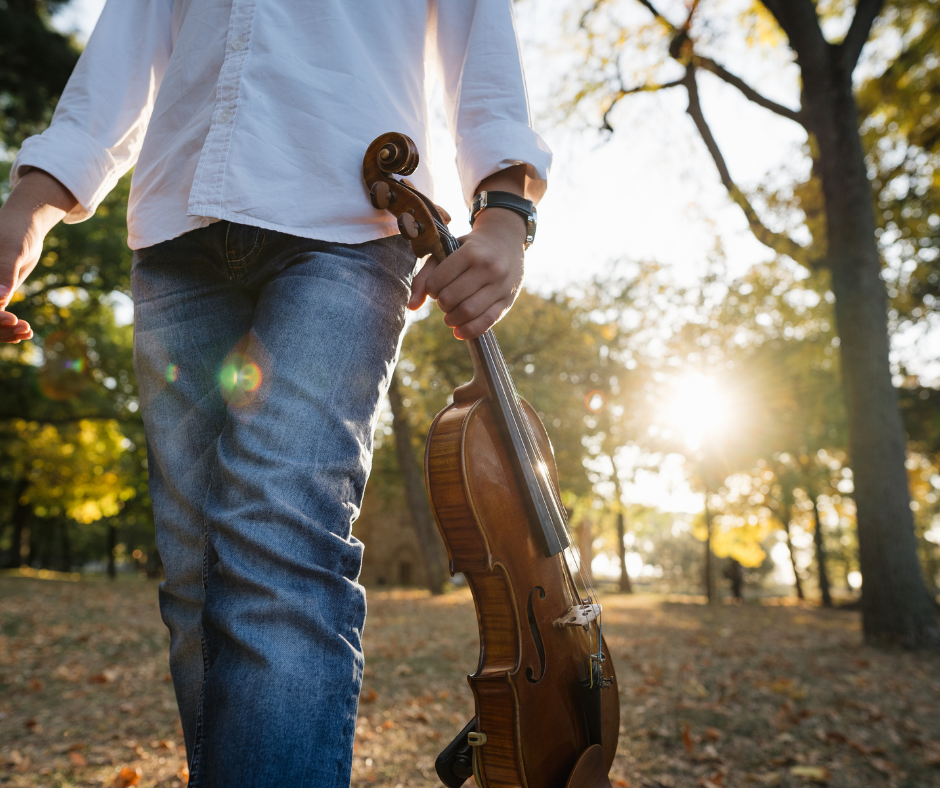 boy walking outside with violin